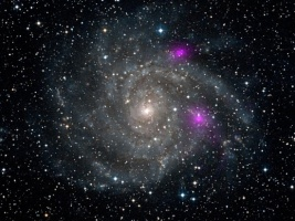 The two magenta spots are blazing black holes in the IC 342 spiral galaxy.